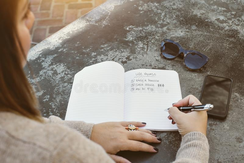 Young Woman Writes Down Her Life Goals and Aspirations in a Journal with Sunglasses and Cell Phone on a Stone Table stock image