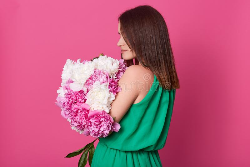 Profile of fragile beautiful young lady posing isolated over pink background in studio, wearing green summer dress, holding her. Present in both hands, feeling stock photos