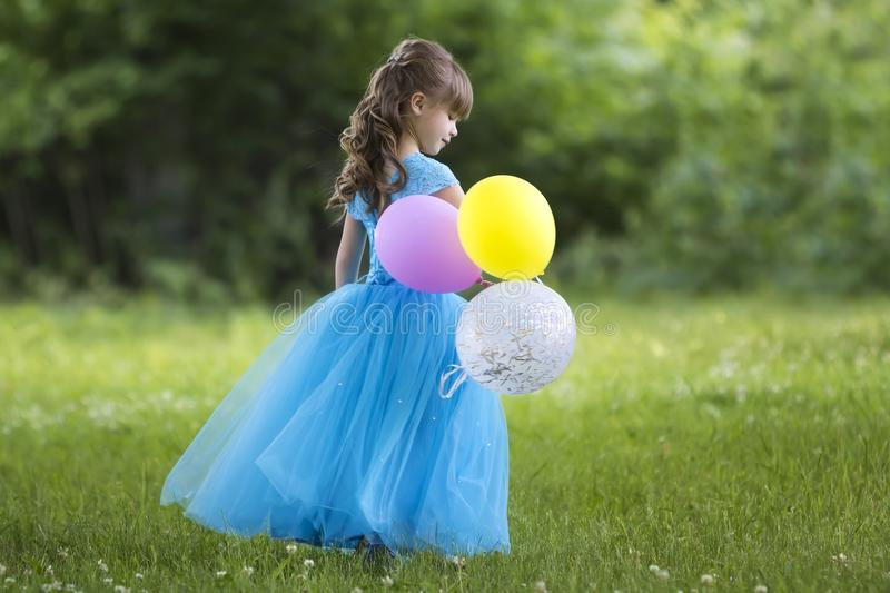 Profile full-length portrait of pretty little blond long-haired girl in long blue dress with colorful balloons standing in bloomin. G field on blurred green stock photography