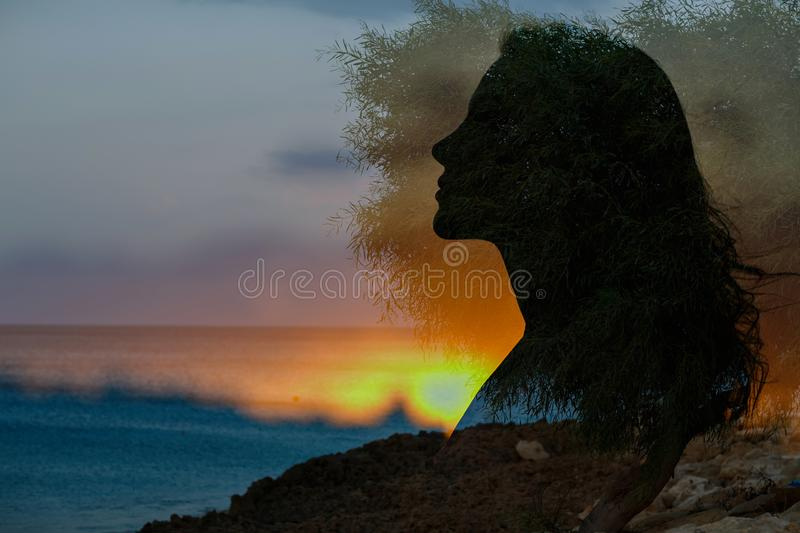 Profile of a girl on the background of the sea and sunset, silhouette, multi-exposure. Double frame royalty free stock image