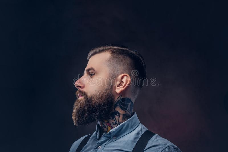 Profile of a handsome old-fashioned hipster in a blue shirt and suspenders. royalty free stock photography