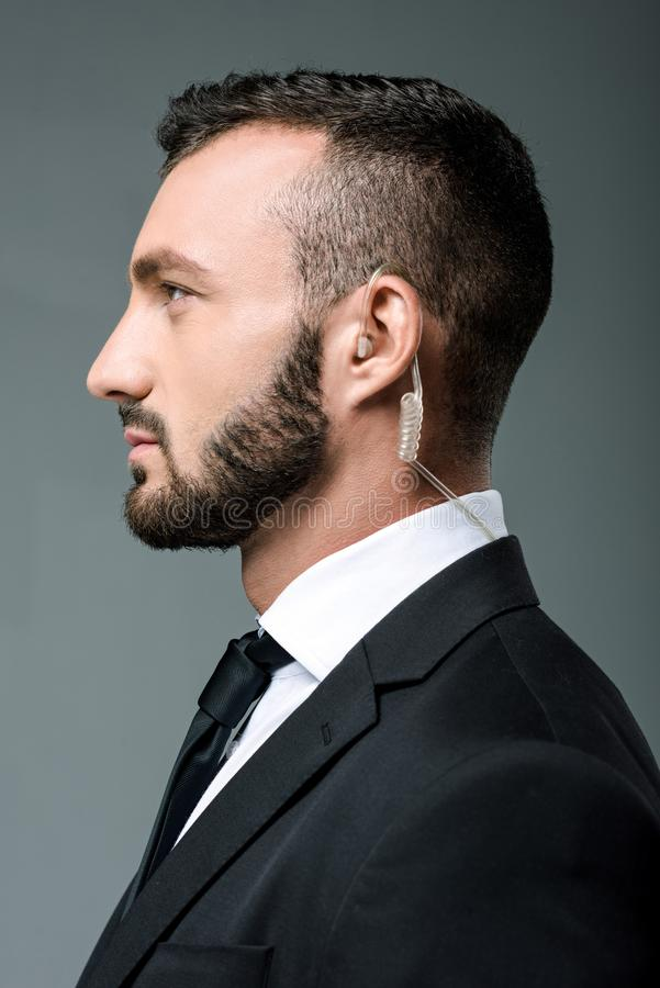 profile of handsome security guard with security earpiece stock photography