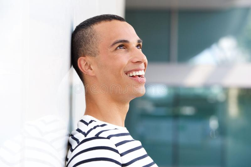 Profile happy young man leaning against white wall stock photography