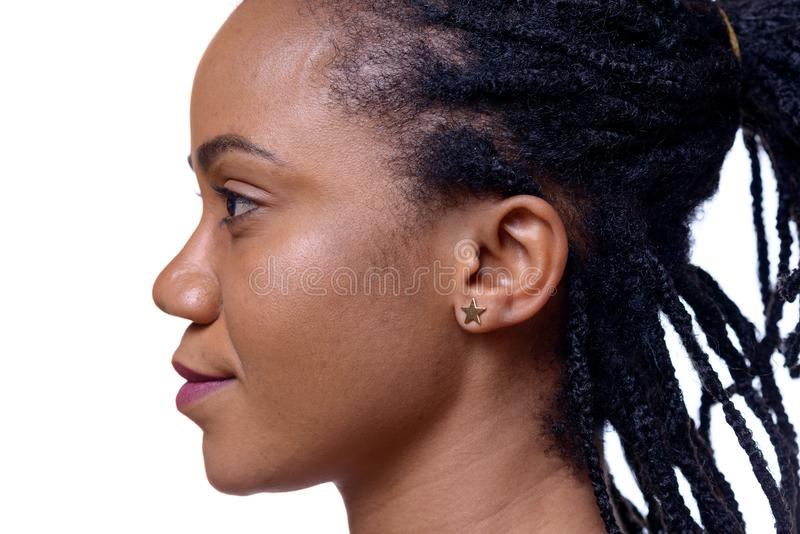 Profile headshot of dark-skinned woman. Against white background, close up view royalty free stock image
