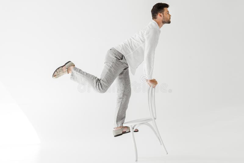 profile of male model in linen clothes balancing on chair royalty free stock photos