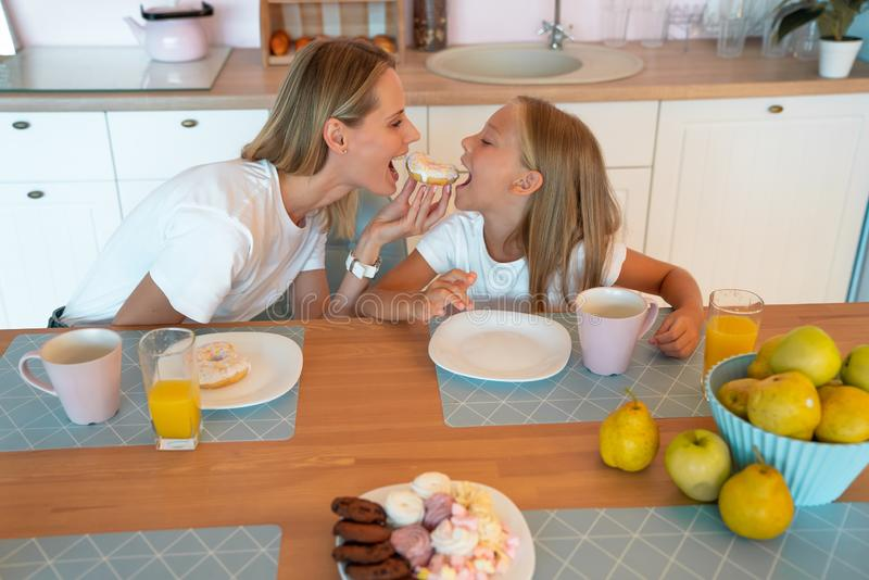 Profile of mom and daughter in the kitchen biting the donut on both sides. cute family photo. dressed in white tshirts stock photo