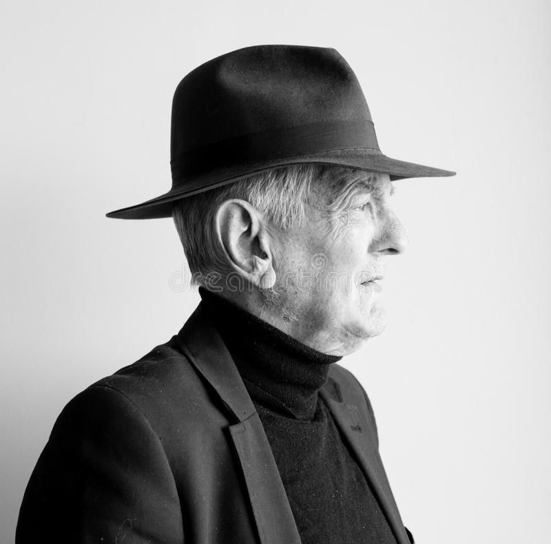 Profile of older man in black hat royalty free stock photography