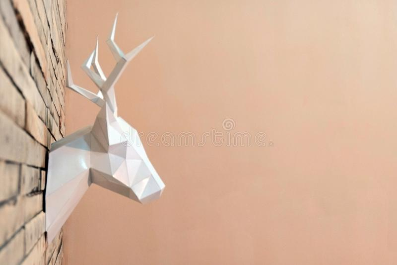 Profile of a paper moose head that hangs on a wooden plank wall. Theme of happy new year and christmas. Copy space. stock photography