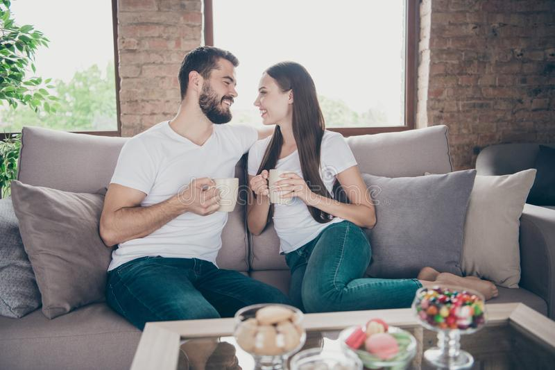 Profile photo of adorable pair in love holding hot beverage hands look eyes sitting cosy sofa indoors stock images