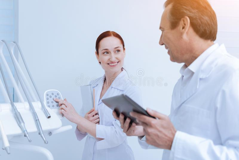 Profile photo of dentist that talking to his intern. Good for you. Pretty assistant keeping smile on her face and touching buttons on apparatus while looking royalty free stock images
