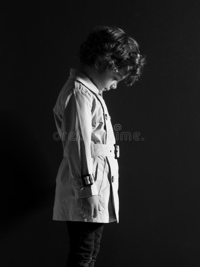 Profile portrait of adorable curly little boy, in raincoat, poses with his head down, isolated on a black background royalty free stock image