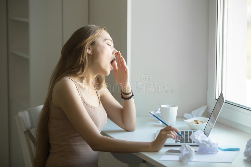 Profile portrait of attractive woman yawning at the laptop. Profile portrait of a young attractive woman in a casual wear yawning at the laptop, , overworked royalty free stock photography