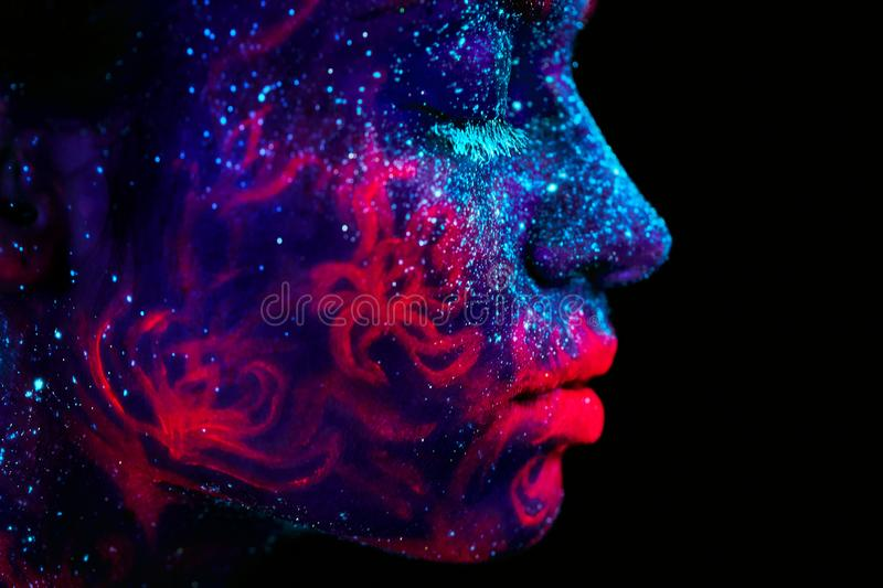 Profile portrait of a beautiful girl alien. Ultraviolet body art blue night sky with stars and pink jellyfish. Bodyart royalty free stock images