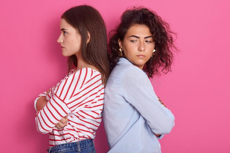 Profile portrait of beautiful girls with dark hair frowning her face in displeasure, wearing casual shirts, keeping arms folded, royalty free stock photo