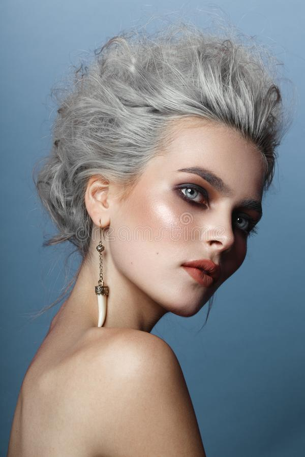 Profile of beautiful young model with gray hairstyle, naked shoulders, makeup, smokey eyes, isolated on blue background. royalty free stock photo