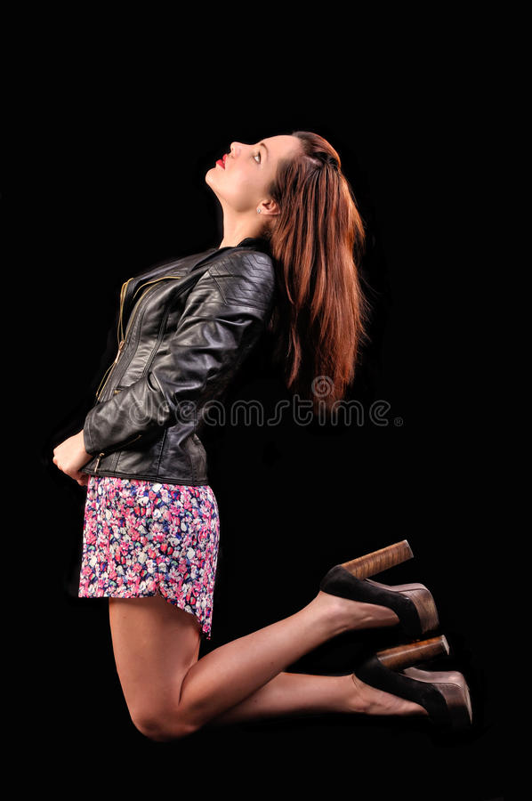 Profile portrait of beautiful young woman sitting on knees on bl royalty free stock image