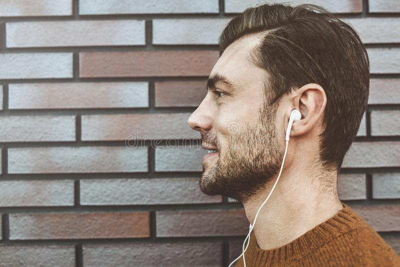 Profile portrait of a cheerful young man, listening to music in headset on mobile phone. Dressed in fashionable clothes. Outdoors stock image