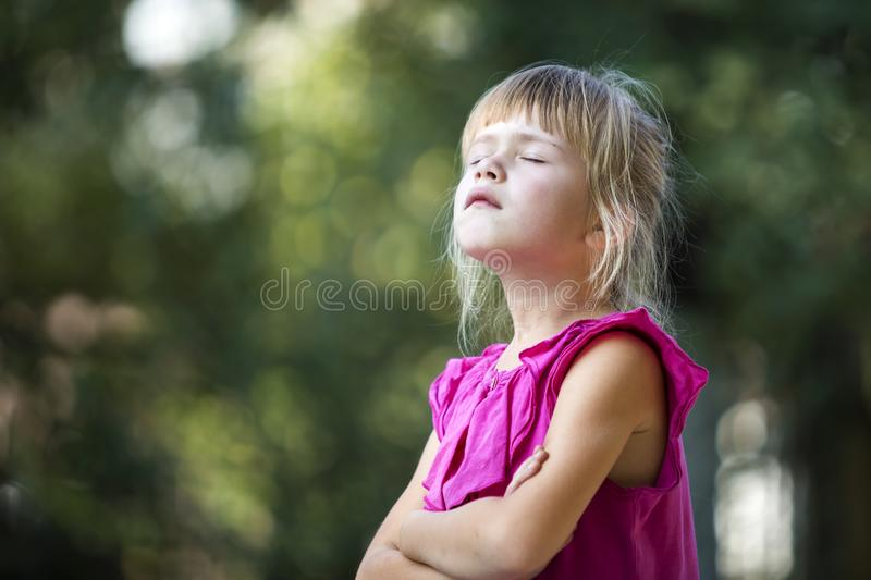 Profile portrait of cute adorable blond child girl in sleeveless pink dress outdoors with raised head and closed eyes on blurred g stock image