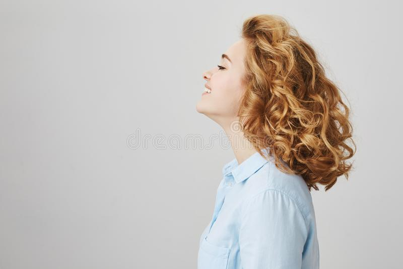 Profile portrait of enjoying happy woman with short curly hair, smiling broadly, wearing casual blue blouse and standing. Against gray background, waiting in stock image