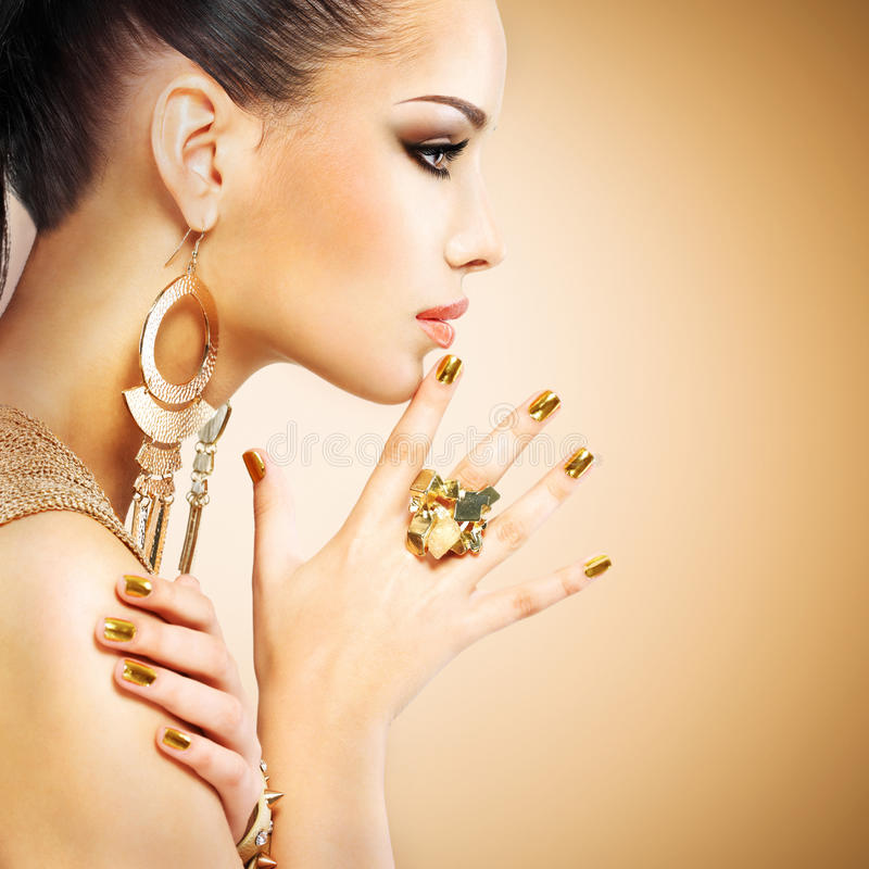 Profile portrait of the fashion woman with beautiful golden mani stock image