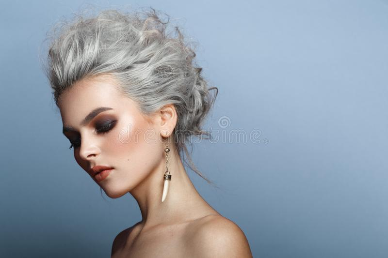 Profile portrait of fashionable, gorgeous young blonde woman, make up, naked shoulders,  on a blue background. royalty free stock photo