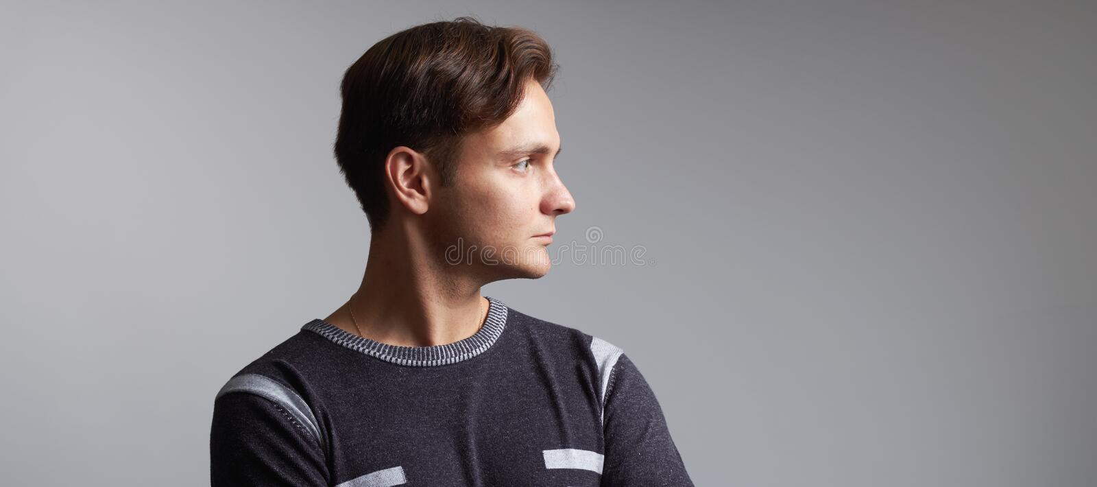 Profile portrait of a handsome man isolated on grey background royalty free stock photo