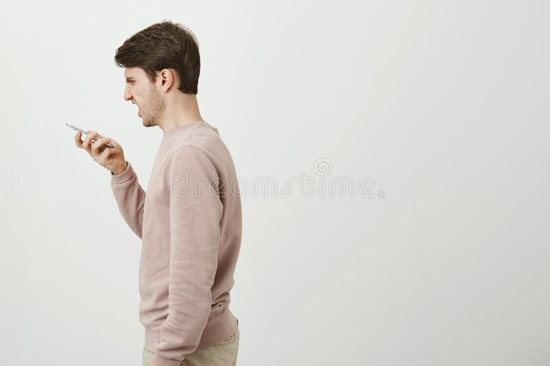 Profile portrait of handsome man with stylish haircut shouting at smartphone, being angry or annoyed while talking on. Speaker. standing against gray background stock image