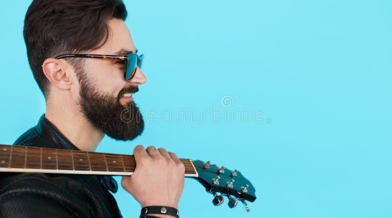 Profile portrait of handsome young male musician. Posing in studio with guitar. Side view of bearded rockstar man holding a guitar royalty free stock photos