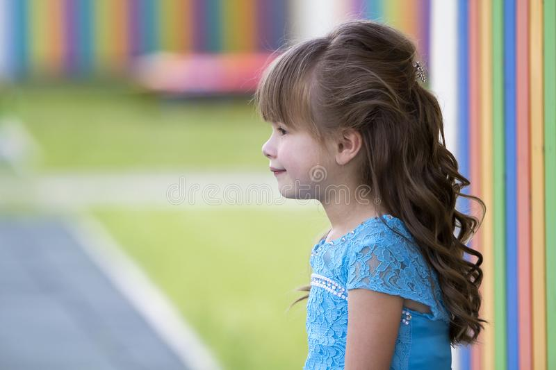 Profile portrait of little fashionable blond girl in blue dress, with gray eyes and beautiful long hair on bright blurred colorful stock photo