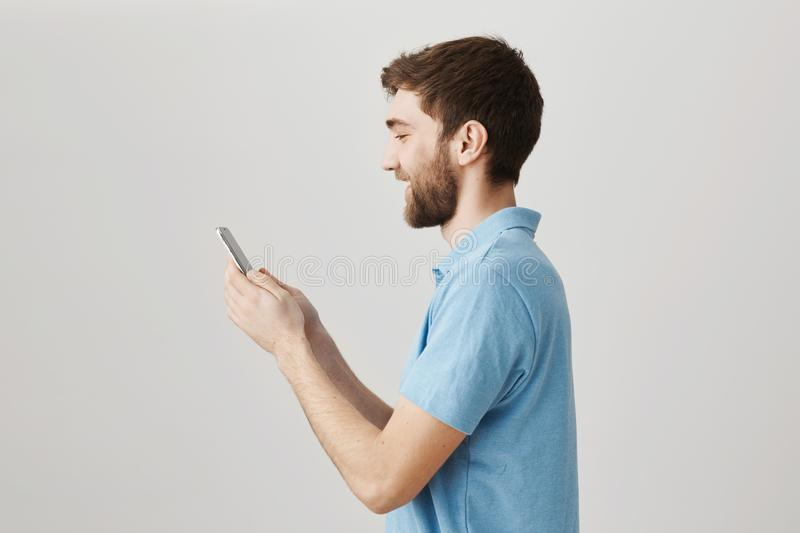 Profile portrait of mature bearded guy looking at screen of smartphone while messaging or playing game, standing with. Joyful smile over gray background royalty free stock photos