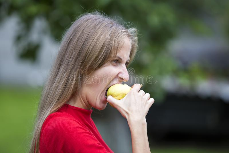 Profile portrait of moody upset angry young woman biting apple. Hard times and problems concept. Profile portrait of moody upset angry attractive blond long stock photos