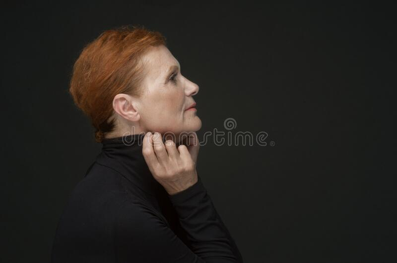 Profile portrait of a red-haired elderly lady in a black sweater on a dark gray background royalty free stock photo