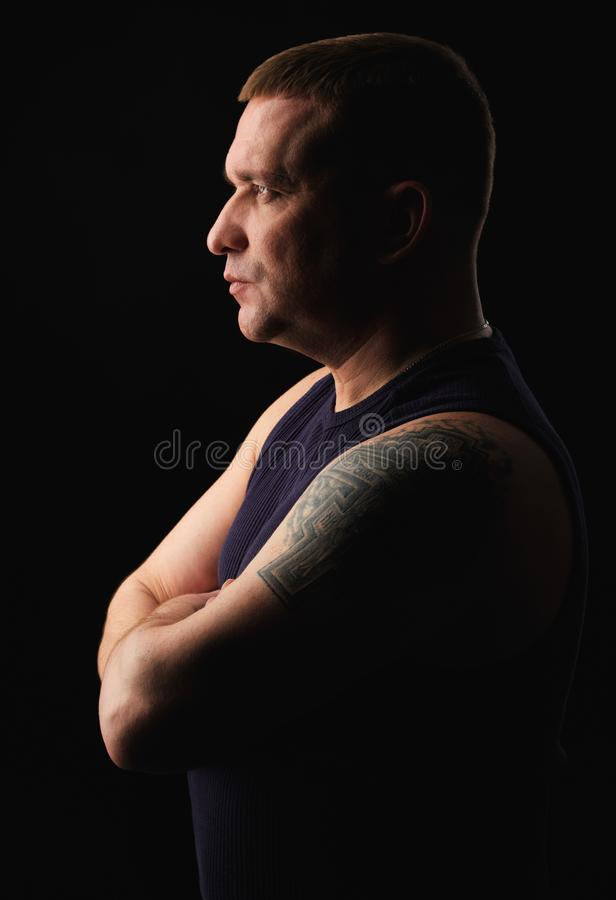 Profile portrait of a serious brutal man with tattoo stock photo