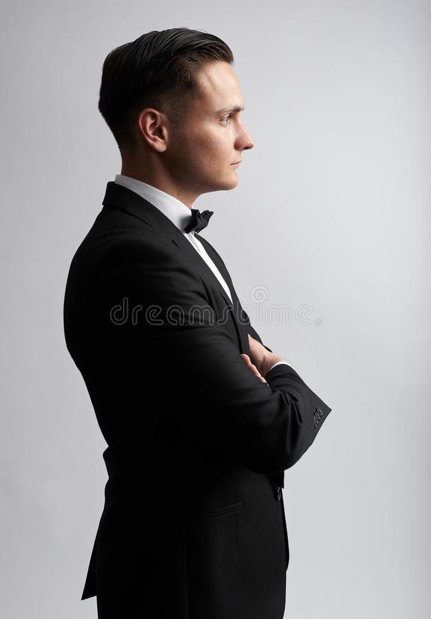 Profile portrait of a sexy man in black suit. Isolated royalty free stock photography