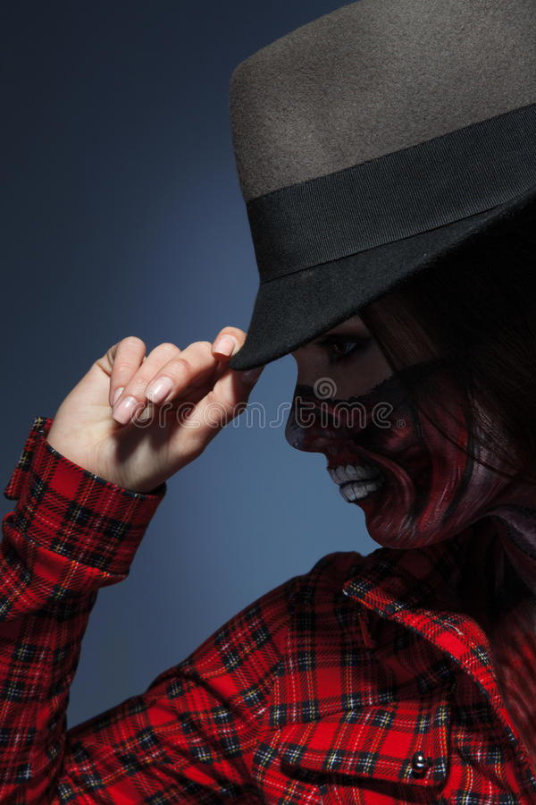 Profile portrait of woman in halloween art on face and hat. In studio stock photography