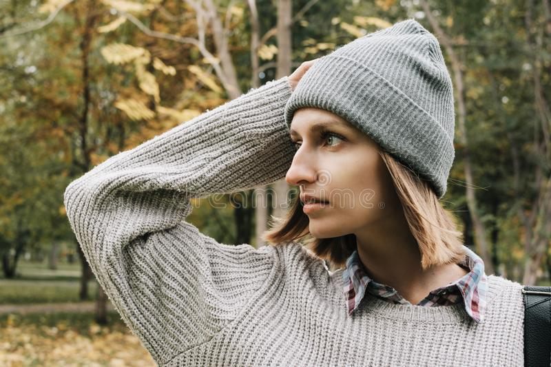 Profile portrait of young adult woman in grey hat and sweater stock photo