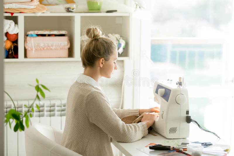Profile portrait of a young attractive woman at sewing machine royalty free stock photos