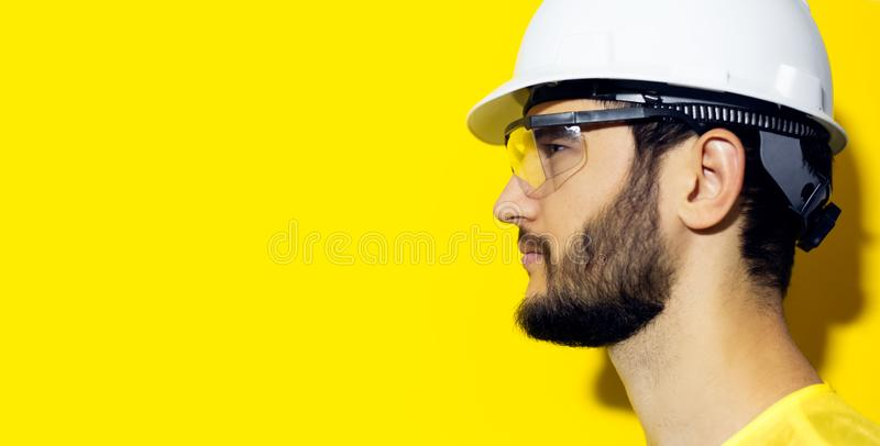 Profile portrait of young bearded man wearing construction safety helmet and glasses on yellow background. Profile portrait of young bearded man wearing stock photography