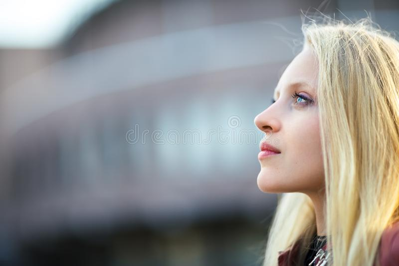 Profile portrait of young beautiful blond woman in city street o stock images