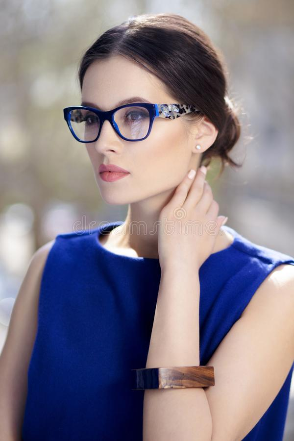 Young beautiful fashionable woman with trendy makeup. Model looking at a side, wearing stylish eyeglasses, blue dress. stock images