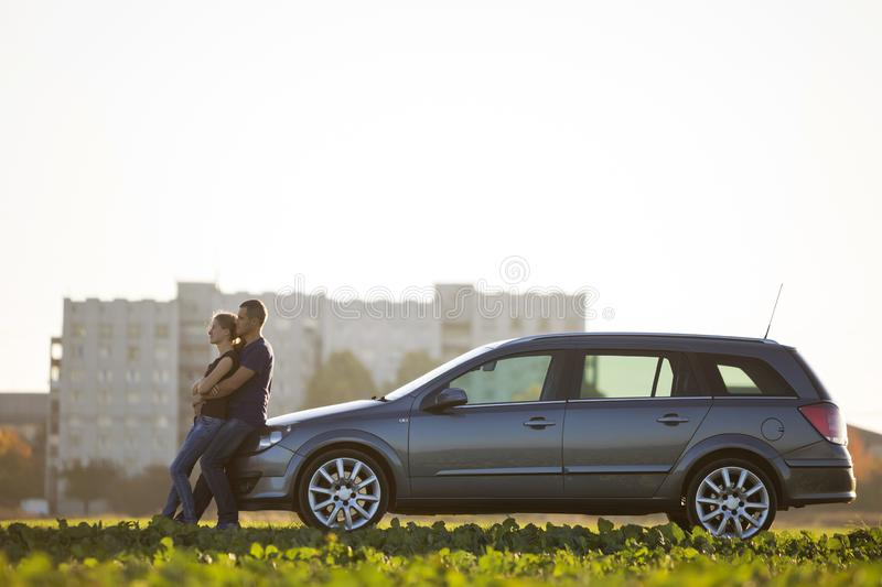 Profile portrait of young couple in love, slim attractive woman and handsome man embraced at silver car in green field on blurred. Profile portrait of young stock image