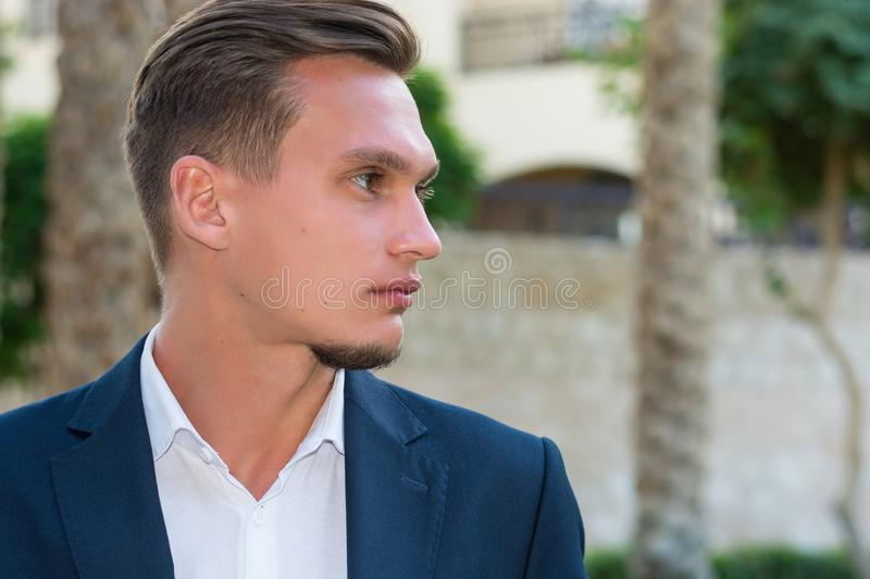 Profile portrait of a young handsome man in a white shirt, white trousers and suit stands near the palm tree. Fashion Model stock images