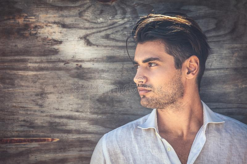 Profile portrait of young and handsome man on wooden background. stock image