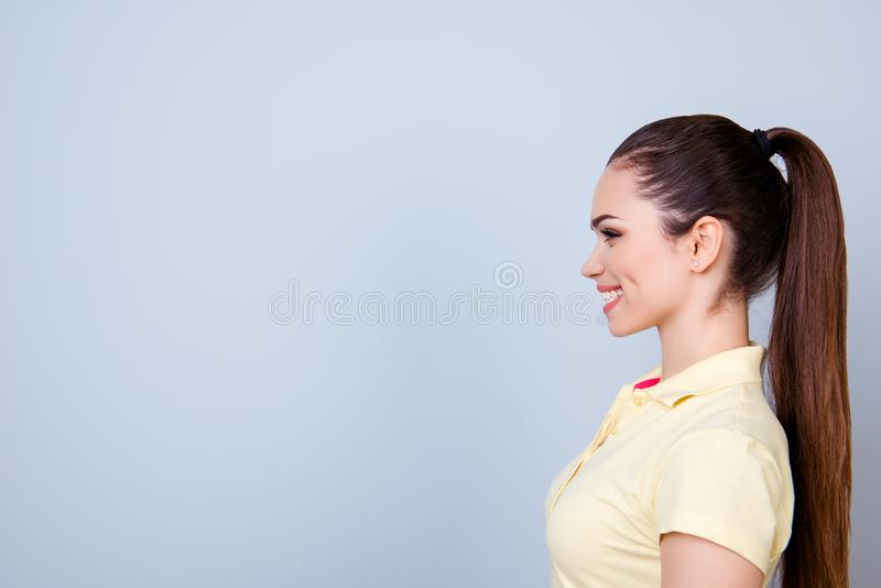 Profile portrait of young lady in yellow tshirt with ponytail, t stock photo
