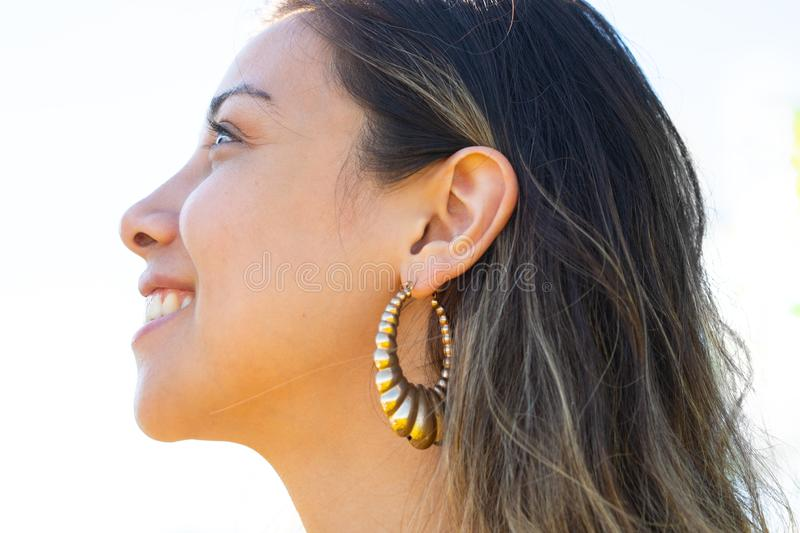 Close up profile portrait of an attractive, woman with long hair and earrings stock photography