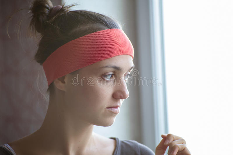 Profile portrait of a young woman alone looking out window. royalty free stock photography