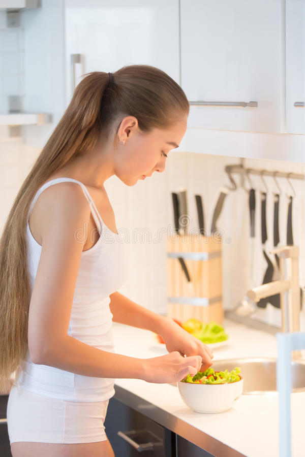 Profile portrait of a young woman making salad on the kitchen. Young woman with long braid standing at the kitchen and making green salad, wearing underwear royalty free stock image
