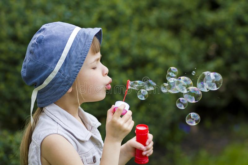 Profile of pretty small preschool blond girl with funny serious. Expression blowing colorful transparent soap bubbles outdoors on blurred green summer stock photo