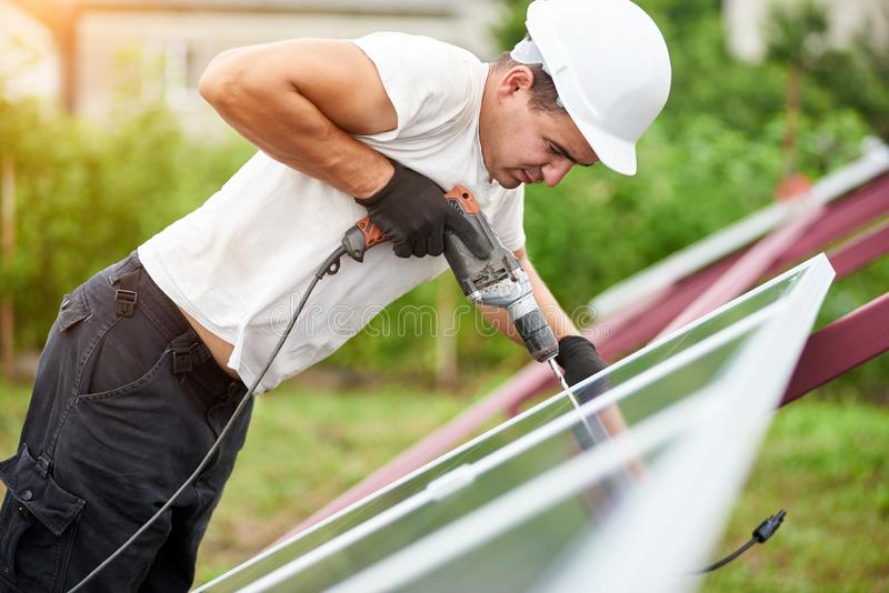 Installation of stand-alone exterior photo voltaic panels system. Renewable green energy generation. Profile of professional technician working with screwdriver stock image