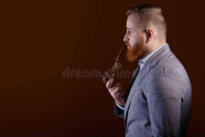 Man smoking a pipe. Profile of a red bearded man smoking a pipe on a brown background stock image